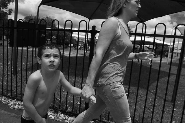 Una mare amb actitud airada porta un nen de la mà